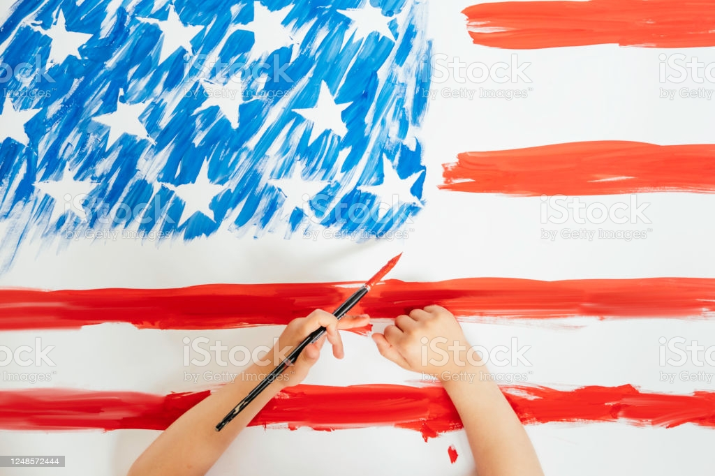 The child hands drawing the American flag. Concept of independence day, July 4.